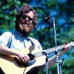 Loudon Wainwright III playing acoustic guitar and wearing a beard